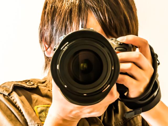 カメラを正面に構えて顔を隠している写真